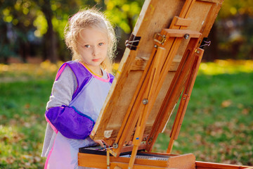 Blond little girl drawing on the easel outdoor in summer park. the child paints. Open air activity for school age children concept.