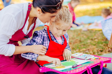 Young female teacher and happy girl in red aprons are painting outdoor in the park. Open air activity for school age children concept.
