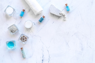 Dead sea cosmetics layout. Sea salt in bottles and bowls near small shells on white stone background top view copy space