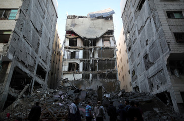 Palestinians gather near the remains of a building that was completely destroyed by an Israeli air strike, in Gaza City