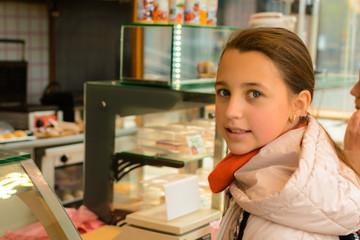 A girl in a street shop buys Belgian waffles