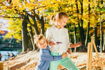 Children drawing with colorful paints outdoor in autumn park. Creative brother and sister painting on nature. Open air activity for different age children concept.