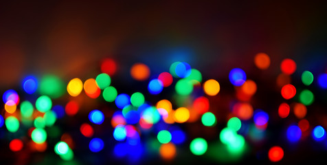 Colorful bokeh out of focus christmas lights circles on dark background.