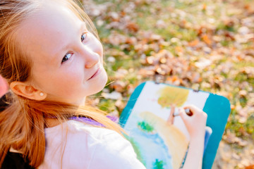 Blond haired teenager school girl drawing beautiful picture outdoor in the park at sunset. Open air activity for school age children concept. Close up