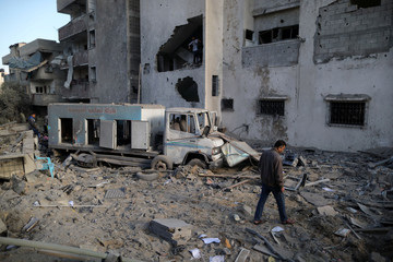 Palestinian man walks at the site of an Israeli air strike on Hamas's TV station building, in Gaza City