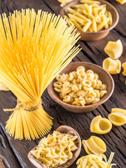 Different pasta types on wooden table.
