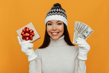 Christmas presents. Woman portrait. Accessories. Asian girl in a white polo neck, cap and gloves is holding a gift box and money and smiling, on an orange background
