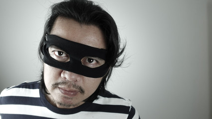 Robber man with black mask thinking about plotting for robbery, Thief robbery concept