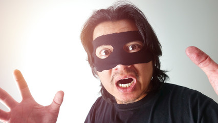 Robber man with black mask  were shocked when they got caught,Thief robbery concept