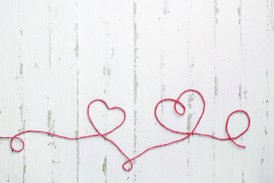 Red thread and two hearts on light wooden background