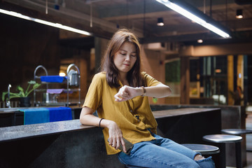 Serious young worried woman holding phone sitting in a cafe and looking at her watch while waiting for her friend or her boyfriend.