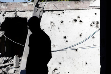 A man is silhouetted as he stands near a house damaged by a rocket fired from the Gaza Strip, in the Israeli city of Ashkelon