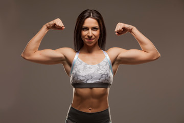 Pretty muscular young woman posing on gray background