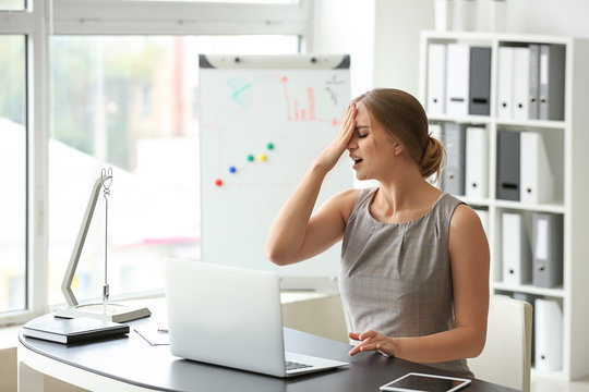 Emotional young woman after making mistake during work with laptop in office