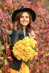 Beautiful young woman with yellow flowers in autumn park