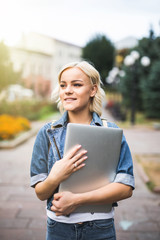 Happy blonde woman in jeans jacket holding laptop computer outdoors