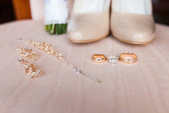 three golden wedding rings on pink background