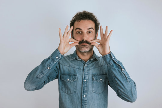 Funny portrait of brown, smiling, handsome man touching his mustache. Jeans shirt. Gray background.