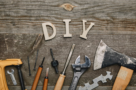Flay lay with different carpentry tools and diy sign on wooden background