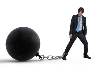 Young businessman has chained big metal ball to his leg. Isolate