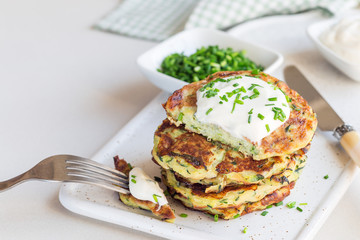 Vegetarian zucchini fritters or pancakes, served with greek yogurt and green onion on a ceramic plate, horizontal, copy space