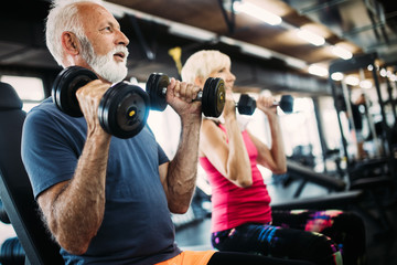 Fit senior sporty couple working out together at gym Wall mural