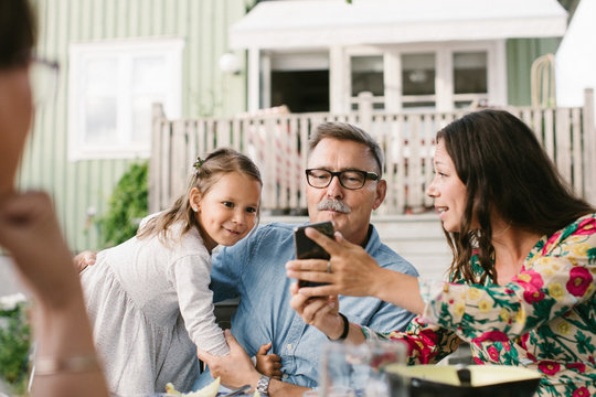 Mid adult woman showing mobile phone to family while sitting in backyard