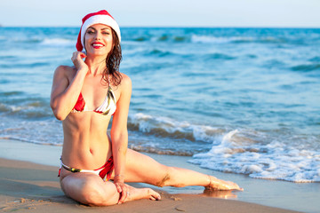 Beautiful young  woman in colorful bikini wearing the Christmas red santa's hat on her winter new year's vacations on a tropical beach coast line