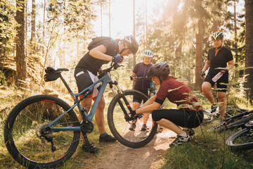 Women repairing mountain bike on dirt road in forest