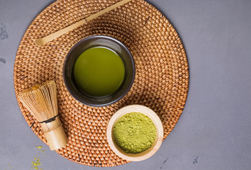 Wall Mural - Matcha tea in a traditional bowl, whisk and powder.
