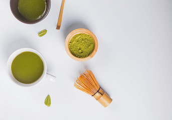Wall Mural - Matcha tea in a cup, whisk and powder on the white background