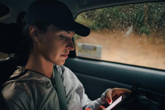 Female athlete using smartphone while traveling in car during rainy season
