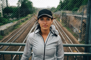 Portrait of female athlete standing against fence on bridge