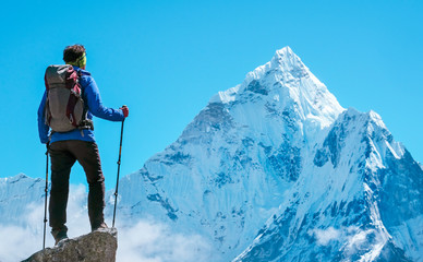 Hiker with backpacks reaches the summit of mountain peak. Success, freedom and happiness, achievement in mountains. Active sport concept. Wall mural