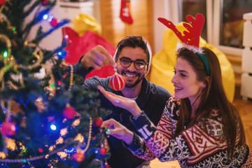 Couple decorating Christmas tree.