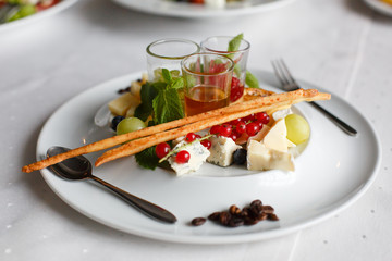 Plate of brie, parmesan, grapes, currants and sauces