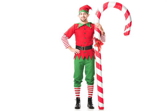 smiling man in christmas elf costume with hand on hips standing near big candy cane isolated on white