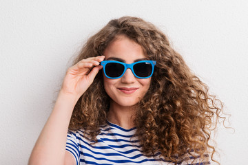 Young beautiful cheerful woman with sunglasses in studio.
