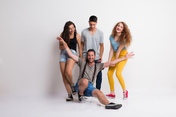 Portrait of joyful young group of friends standing in a studio.