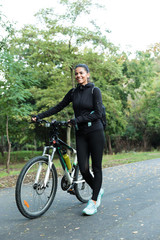 Beautiful woman walking on bicycle in the park outdoors.
