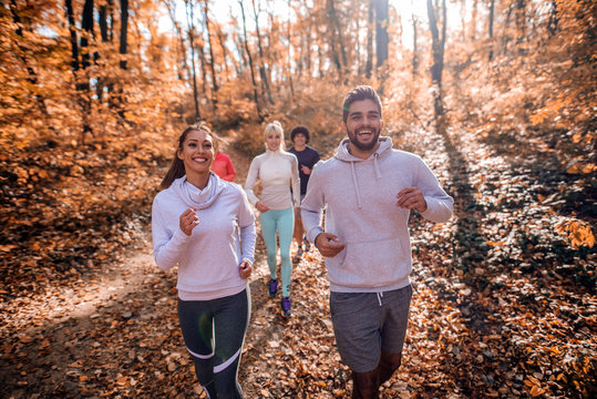 Small group of people running in woods.