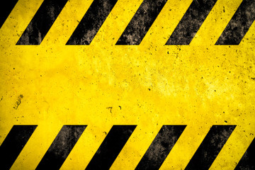 Warning background with yellow and black stripes painted over yellow concrete wall facade texture and empty space for text message in the middle. Concept image for caution, danger and hazard.