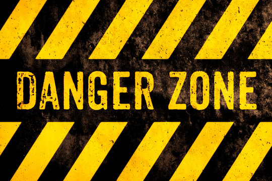 Danger zone warning sign text with yellow and black stripes painted over concrete wall surface facade cement texture background. Concept image for caution, risky dangerous area and hazard.