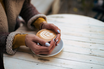 Young woman holding coffee cup with latte art on wooden table. Close-up.