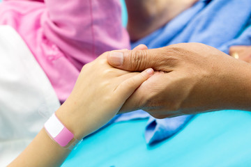 hand hold patient's hand with ID bracelet