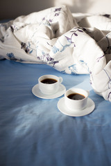 two cups of coffee in bed, sunlight.