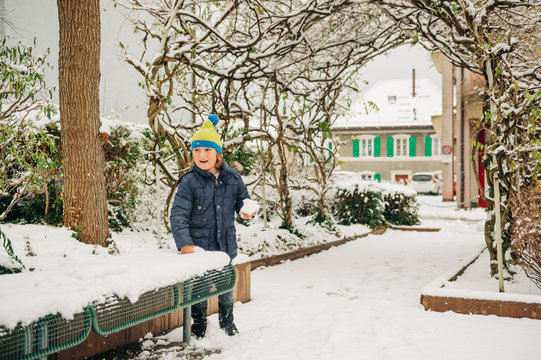 Outdoor portrait of funny little boy having fun under heavy snowfall