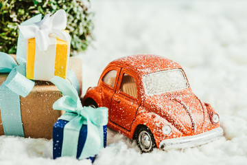 close-up shot of toy car with presents and christmas tree standing on snow made of cotton