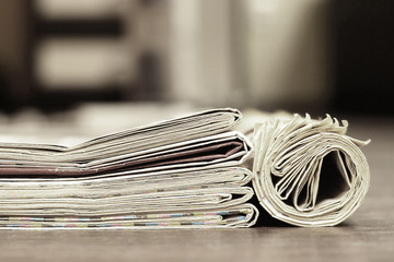 Close up texture of folded and rolled newspapers on wooden table, retro news background