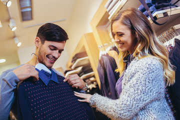 Young man consults with girlfriend while selecting a sweater
